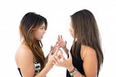Two pretty sisters arguing on white background