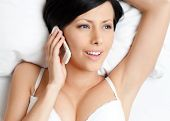 Woman in underwear speaks on telephone while lying in the bedstead, white background
