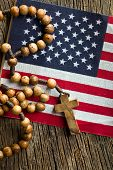 top view of rosary beads with american flag on wooden background