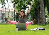 Happy Woman With Computer In An Urban Park