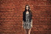 beautiful girl near red brick wall