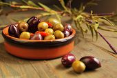 foto of kalamata olives  - Variety of olives into in a ceramic bowl  and three olives in foreground on wooden table - JPG