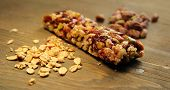 Granola bar with nuts, dry fruits and muesli on a wooden table