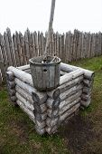 picture of stockade  - Wooden frame old well with a bucket on a background of a stockade isolated on white - JPG