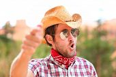 Cowboy man with sunglasses and cowboy hat pointing at camera saying WE WANT YOU. Male model in ameri