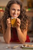 Happy Young Woman Drinking Ginger Tea With Lemon