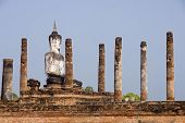 Buddha Statue Sitting Among The Ruins Of Old Sukhothai