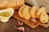 Fresh bread - ciabatta chili and garlic on old wooden board