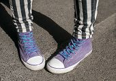 Girl legs with purple sneakers