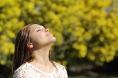 image of breathing exercise  - Woman breathing deep in spring or summer with a yellow background - JPG