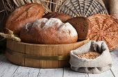 Rye bread on wooden stand on wicker background
