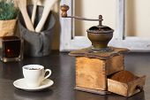 pic of coffee grounds  - Old vintage manual coffee mill or grinder with a drawer full of freshly ground coffee beans standing on an old wooden kitchen counter with a cup and saucer ready to brew a morning drink - JPG