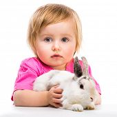 baby girl in a pink T-shirt with her small white rabbit isolated on white background