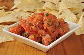 stock photo of gallows  - A small dish of Pico de Gallow with corn tortilla chips in the background - JPG