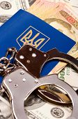 Close-up international Ukrainian passport with handcuffs and US dollars