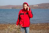 Young Blond Man In Red Jacket Talk On Mobile Phone.