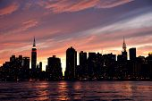 New York City Manhattan midtown silhouette panorama at sunset with skyscrapers and colorful sky over