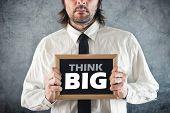Businessman Holding Blackboard With Think Big Title