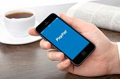 Male Hand Holding A Iphone With App Paypal On A Screen