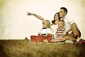 Nostalgic retro image of a young family with kids having picnic on green grass meadow in nature
