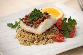 stock photo of halibut  - Baked halibut with olive tapenade crust garnished with couscous fried cherry tomatoes and fresh parsley - JPG