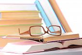 Composition with glasses and books, isolated on white