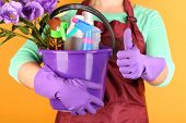 Housewife holding bucket with cleaning equipment on color background. Conceptual photo of spring cleaning.