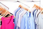 Different clothes on hangers, on gray background