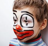 stock photo of pantomime  - little cute boy with facepaint like clown - JPG