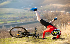 stock photo of biker  - Mountain Biker has a painful looking crash with his bike - JPG