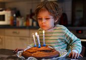 Adorable Four Year Old Boy Celebrating His Birthday And Blowing