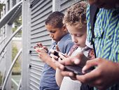 stock photo of addict  - Three boys using a smartphone after school - JPG