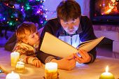 Young Father And His Little Son Reading Book By A Fireplace On Christmas