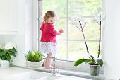 Cute Toddler Girl In A Red Dress Watching Out A Window In A Beautiful White Sunny Kitchen