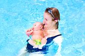 Young Active Woman And A Funny Baby Boy Having Fun In A Swimming Pool