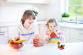 Happy Teenager Boy And His Cute Toddler Sister Having Fruit For Breakfast