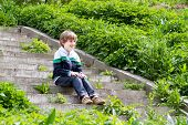 Little Boy Playing On The Stairs On A Garden