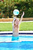 Little Boy Playing With A Ball In A Swimming Pool