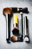 stock photo of bristle brush  - Various makeup brushes on dark background - JPG