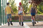 image of inline skating  - Outdoor portrait of group of friends with roller skates and bike riding in the park - JPG