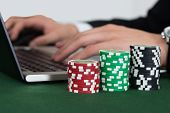 Businessman Using Laptop By Stacked Casino Chips