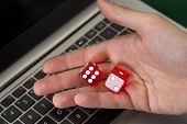 Businessman Holding Red Dices While Using Laptop