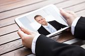 picture of video chat  - Cropped image of businesswoman video conferencing with colleague on digital tablet outdoors - JPG
