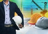 Engineering Man Standing With White Safety Helmet Against Building And Crane Construction Working Ta