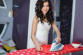 Happy woman ironing at ironing board in home