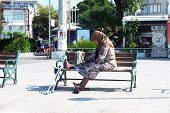 Elderly woman sits alone on bench
