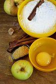 ingredients for baking apple pie (flour, egg, sugar, cinnamon, apples)