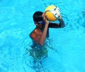 Boy throws a ball in swimming ball