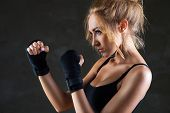 Young beautiful sexy boxer woman striking pose with boxing bandage on hands over gray background