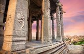 picture of karnataka  - Carved columns with Hindu deities in ancient temple at sunset violet sky in Hampi Karnataka India - JPG